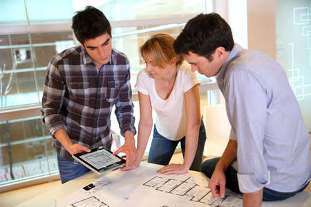 Startup business team working on blueprint photo
