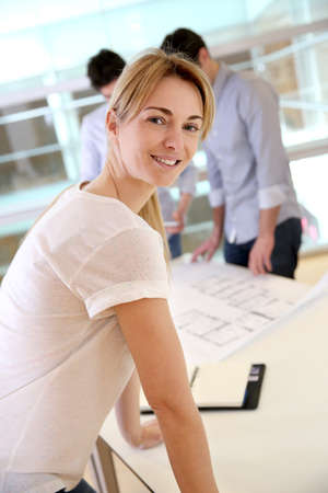 group plan: Cheerful architect woman looking satisfied