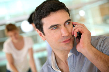 reunion de trabajo: Hombre de negocios en el tel�fono durante la reuni�n de trabajo Foto de archivo