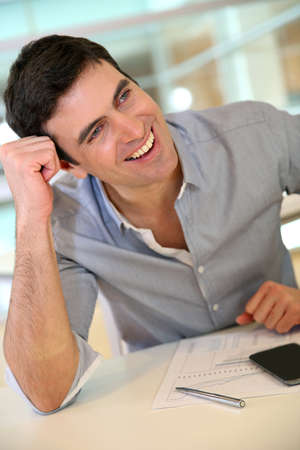 joking: Man at work in office joking with colleague
