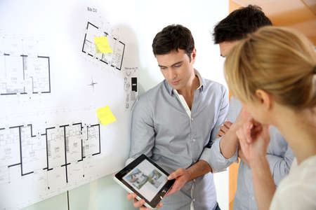 group plan: Architects in office looking at construction project