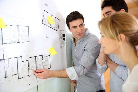Architects in office looking at construction project photo