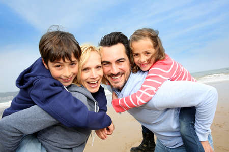 shoulder ride: Portrait of cheerful family at the beach