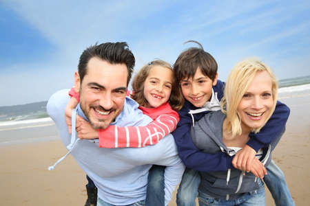 holding family together: Portrait of cheerful family at the beach