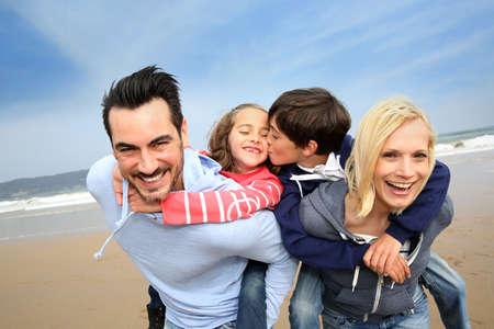 shoulder ride: Retrato de la familia alegre en la playa Foto de archivo