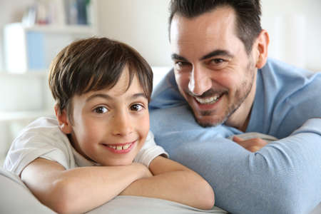 Portrait of father and son relaxing at home photo