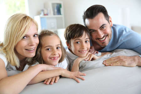Family of four sitting in sofa at home Stock Photo - 18919051