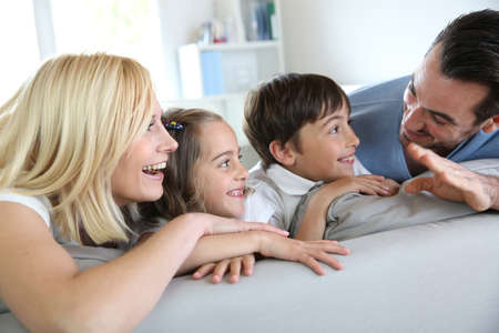 Family of four sitting in sofa at home Stock Photo - 18919023