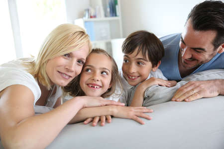 Family of four sitting in sofa at home Stock Photo - 18919027