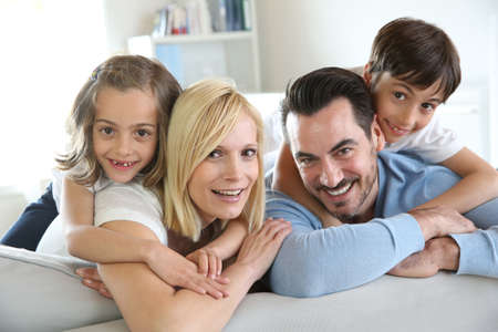 Family of four sitting in sofa at home photo