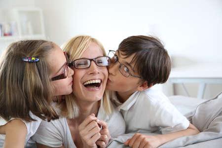 Portrait of children kissing her mom