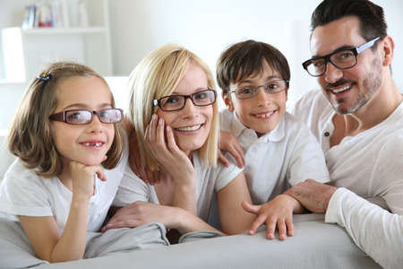 family on couch: Family of four wearing eyeglasses