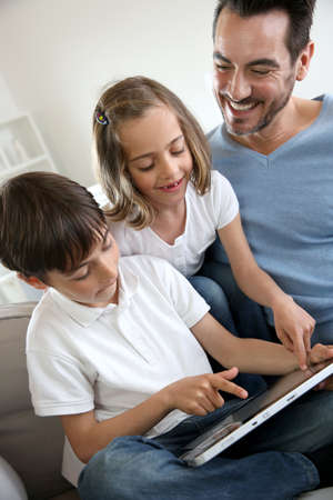 Children with daddy at home using digital tablet photo