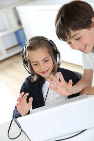 Portrait of kids waving at webcamera with laptop photo