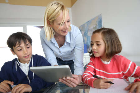 Teacher in class with kids using electronic tablet Imagens