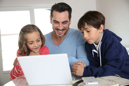 computer control: Man with children using laptop at home Stock Photo