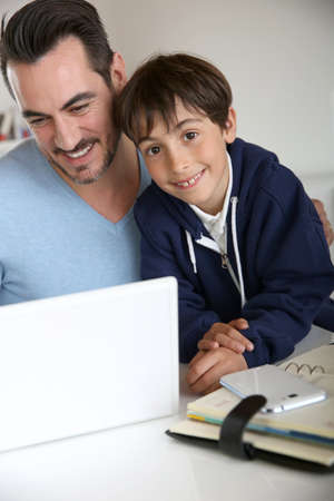 Man showing to young boy how to use laptop photo