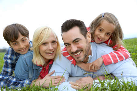 Family of four relaxing in countryside photo