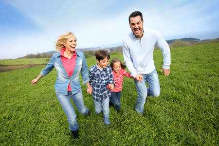 Family of four running together in natural landscape photo