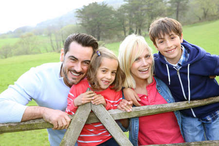 Family leaning on a fence in countryside photo