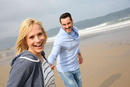 couple laughing: Cheerful woman running with husband on the beach Stock Photo
