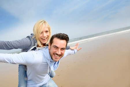 shoulder ride: Pareja de edad media que se divierte en una playa de arena Foto de archivo