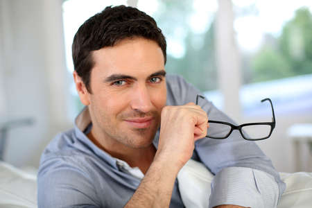 wearing glasses: Good-looking man with eyeglasses sitting on sofa