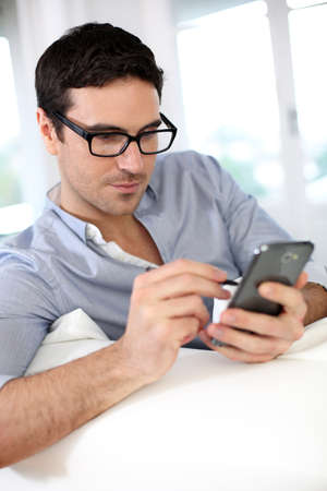 35 years old man: Man sitting in sofa and using smartphone Stock Photo