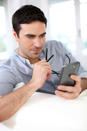 dark eyes: Man sitting in sofa and using smartphone Stock Photo