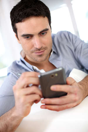 35 years old: Modern guy using martphone at home Stock Photo