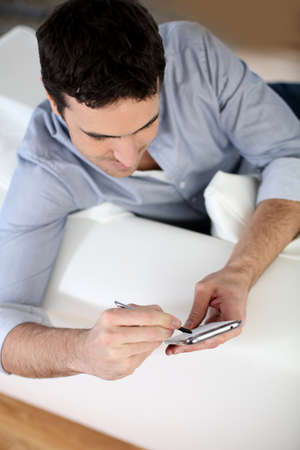 35 years old: Upper view of man in sofa using smartphone