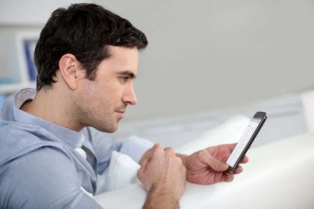 35 years old: Profile view of man connected on smartphone