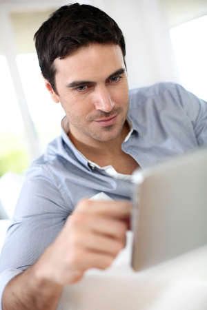 35 years old: Man websurfing on internet with digital tablet