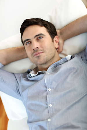 arms behind head: Man relaxing in sofa with arms behind head Stock Photo
