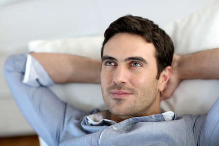 Man relaxing in sofa with arms behind head photo