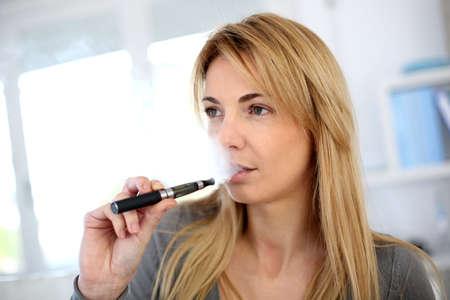 cigarette smoke: Donna di fumare con la sigaretta elettronica Archivio Fotografico