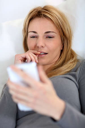 35 years old: Woman writing short message on smartphone Stock Photo
