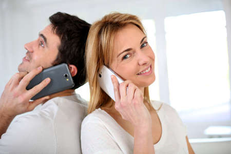 phonecall: Couple using smartphone, sitting back to back
