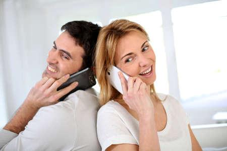 Couple using smartphone, sitting back to back photo