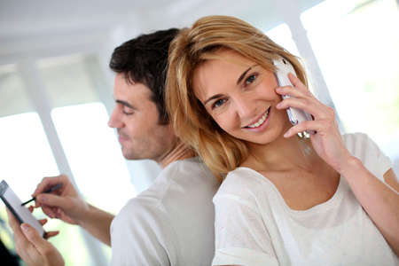 phone conversation: Couple using smartphone, sitting back to back