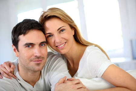 35 years old man: Portrait of in love couple sitting in sofa
