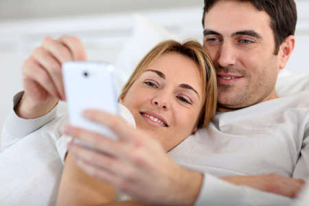 mobile phone adult: Couple laying in sofa and using spartphone