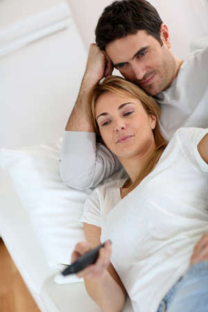 Sweet couple in sofa watching tv photo