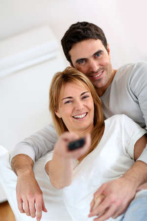 35 years old: Sweet couple in sofa watching tv