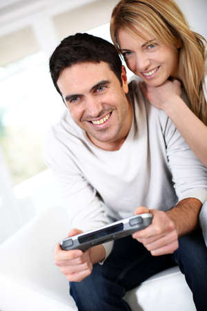 Couple at home playing video games photo
