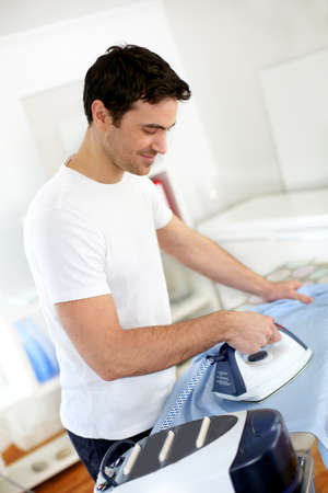 Man ironing shirt before leaving for work photo