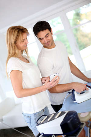 Girl bothering boyfriend while ironing shirt photo