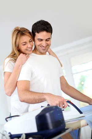 Girl bothering boyfriend while ironing shirt photo
