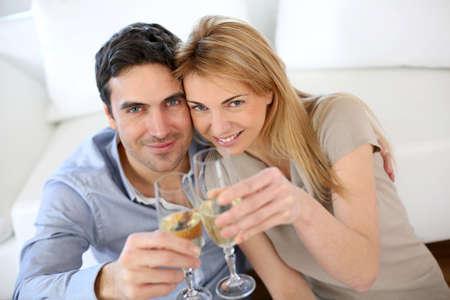 sektglas: Fröhlich Paar feiert mit einem Glas Sekt