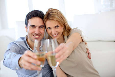 sparkling: Cheerful couple celebrating with glass of sparkling wine Stock Photo